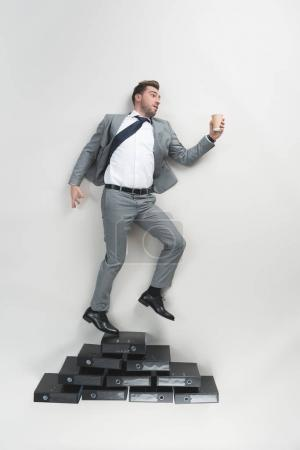 Photo for Overhead view of businessman with coffee to go in hand standing on pile of folders isolated on grey - Royalty Free Image