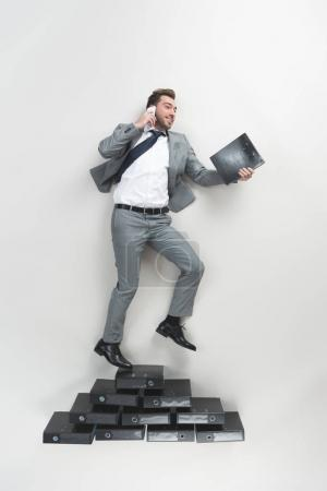 Photo for Overhead view of businessman talking on smartphone while standing on pile of folders isolated on grey - Royalty Free Image