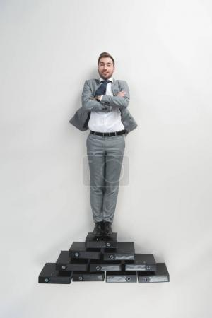 Photo for Overhead view of businessman with arms crossed standing on pile of folders isolated on grey - Royalty Free Image