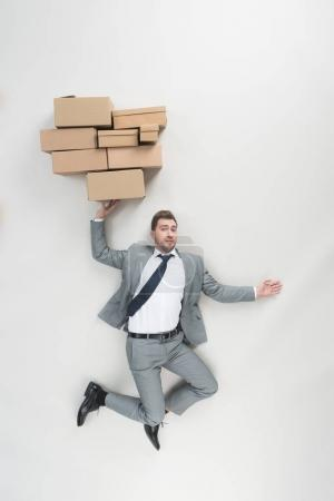 Photo for Overhead view of businessman in suit holding pile of cardboard boxes isolated on grey - Royalty Free Image