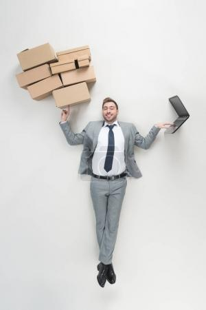overhead view of businessman holding cardboard boxes and using laptop isolated on grey