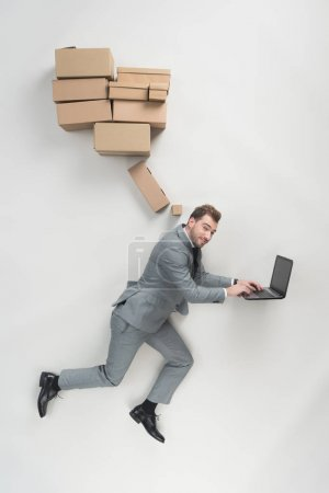 Photo for Overhead view of businessman with cardboard boxes above head using laptop isolated on grey - Royalty Free Image