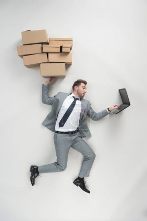 Photo for Overhead view of businessman holding cardboard boxes and using laptop isolated on grey - Royalty Free Image