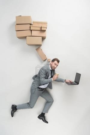 overhead view of businessman with coffee to go in hand using laptop isolated on grey