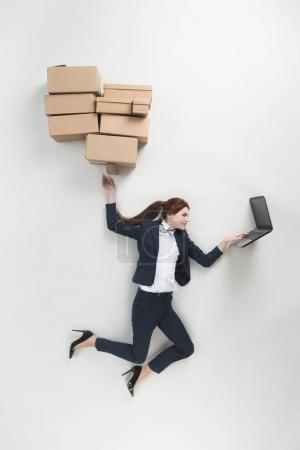 overhead view of businesswoman with cardboard boxes using laptop isolated on grey