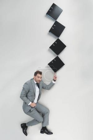 overhead view of businessman holding stack of folders on one finger isolated on grey