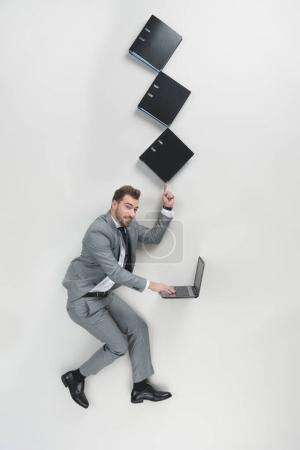 overhead view of businessman with stack of folders on one finger using laptop isolated on grey