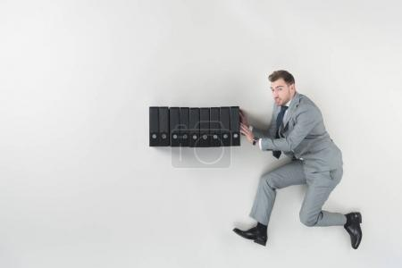 overhead view of businessman pushing folders isolated on grey