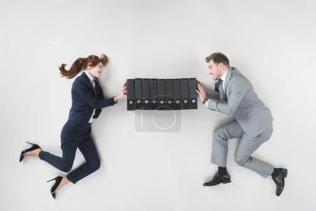 overhead view of smiling businesspeople pushing folders isolated on grey