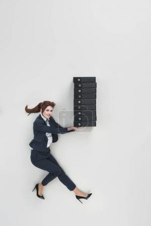overhead view of smiling businesswoman holding pile of folders isolated on grey