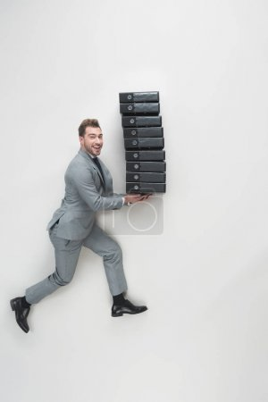 overhead view of young businessman carrying stack of folders isolated on grey