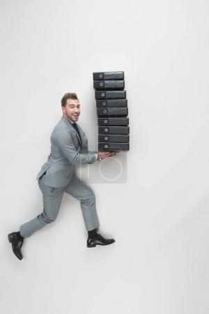 Photo pour Vue aérienne du jeune homme d'affaires transportant la pile de dossiers isolé sur fond gris - image libre de droit