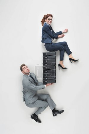Photo for Overhead view of businessman holding smiling businesswoman on pile of folders isolated on grey - Royalty Free Image