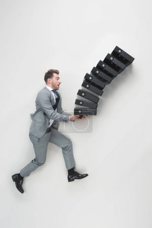 Photo for Overhead view of young businessman carrying stack of falling folders isolated on grey - Royalty Free Image