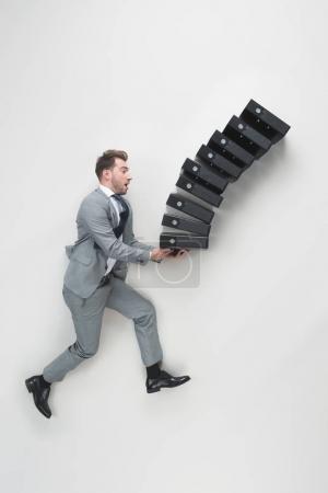 Photo pour Vue aérienne du jeune homme d'affaires transportant la pile de dossiers chutes isolé sur fond gris - image libre de droit