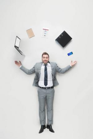 Photo for Overhead view of smiling businessman with outstretched arms and office supplies above head looking at camera isolated on grey - Royalty Free Image