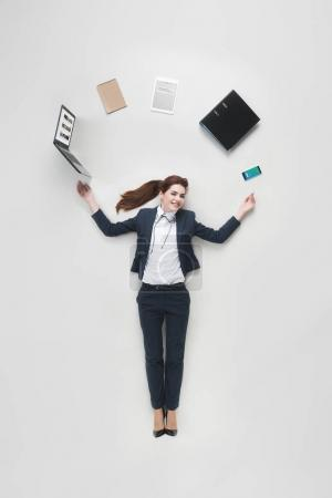Photo for Overhead view of businesswoman with various office supplies using laptop isolated on grey - Royalty Free Image