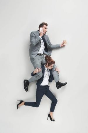 Photo pour Vue aérienne de femme d'affaires transportant l'homme d'affaires qui parle sur smrtphone isolé sur fond gris - image libre de droit