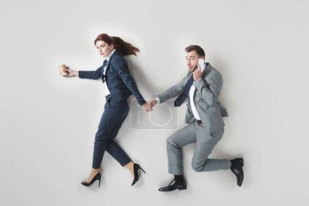 Foto de Vista aérea del empresario hablando por teléfono inteligente mientras mantiene las manos junto con colega aislado en gris - Imagen libre de derechos