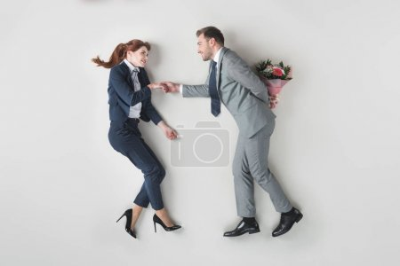 overhead view of smiling businessman going to present flowers to colleague isolated on grey