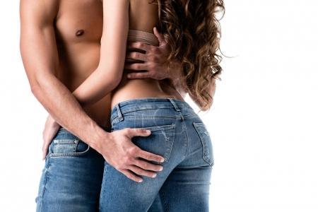 abgeschnittene Rückansicht eines sinnlichen Paares in Jeans isoliert auf Weiß