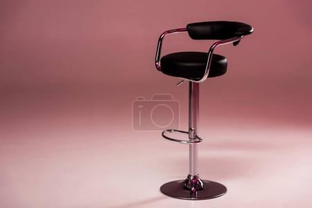 Metallic bar stool infront of pink background