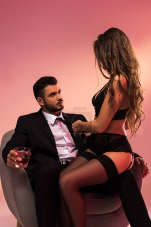 attractive businessman sitting on armchair with beautiful girl in lingerie