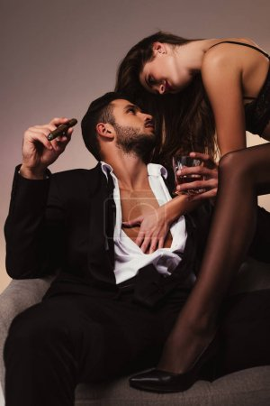 young handsome businessman sitting on armchair with beautiful girl in lingerie