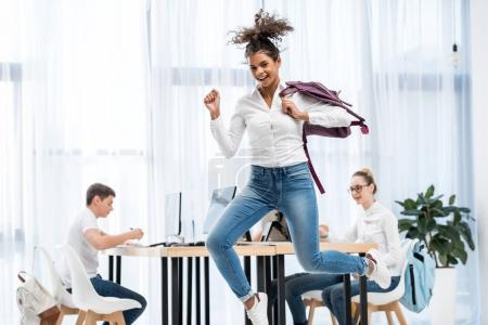 young african american student girl jumping in classroom with friends