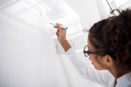 young african american teenager writing on white board