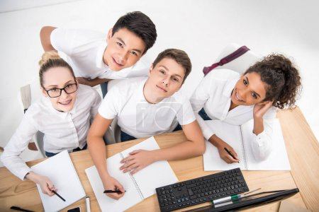 Photo for Young students writing something in notebooks - Royalty Free Image