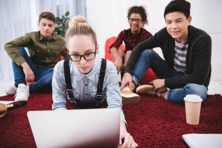 Photo for Young teen students lying on carpet with notebooks and looking at laptop - Royalty Free Image