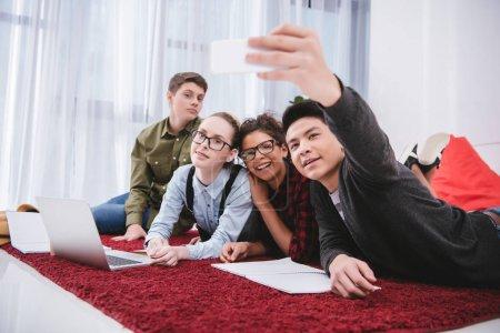 Photo pour Jeunes teen couché sur le tapis et prise selfie - image libre de droit