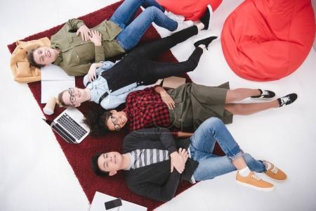 young teen students lying on carpet with notebooks and laptop