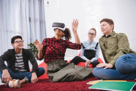 Photo for Young girl in virtual reality glasses sitting on carpet with friends - Royalty Free Image