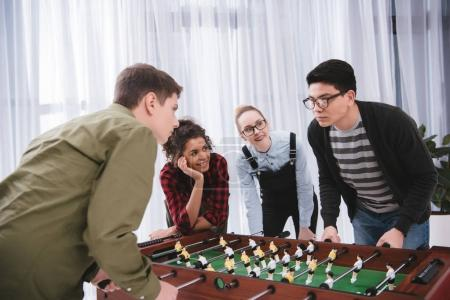 happy young teenagers playing in table soccer