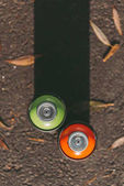 top view of cans with red and green spray paint on asphalt with shadow