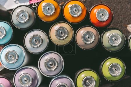 Photo pour Vue de dessus des boîtes de conserve avec la peinture colorée pour graffiti sur asphalte - image libre de droit