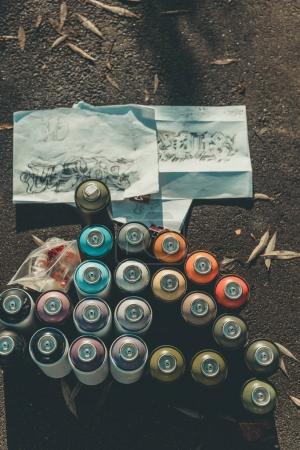 Photo pour Vue de croquis de graffiti et de canettes de dessus d'asphalte painton spray coloré - image libre de droit
