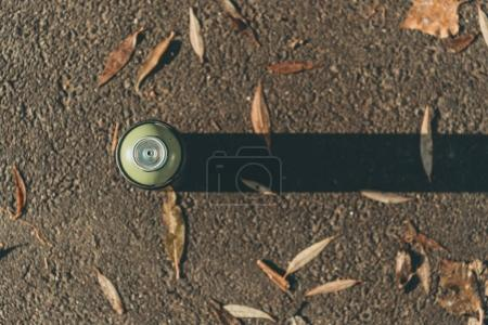 top view of can with spray paint on asphalt with shadow