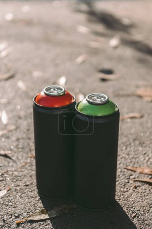 cans with red and green aerosol paint for graffiti on asphalt