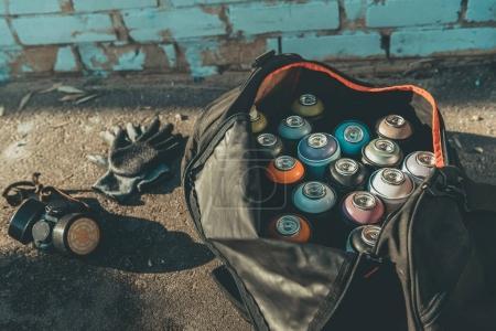 Photo pour Gants et masque respiratoire près de gros sac avec les contenants de peinture en aérosol - image libre de droit
