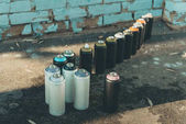 cans with aerosol paint standing in row on asphalt