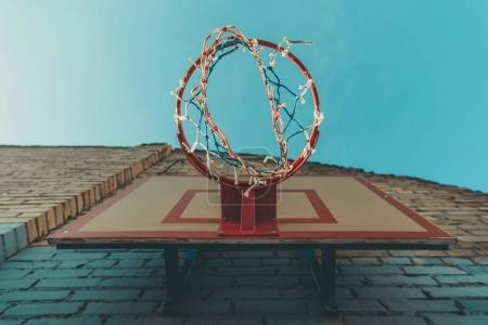 bottom view of basketball hoop on wall with graffiti