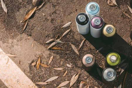 top view of cans with colorful spray paint for graffiti on asphalt