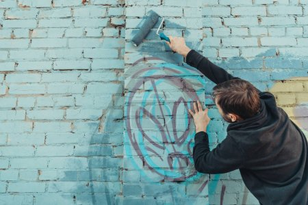 Photo for Male street artist painting colorful graffiti on wall with roller - Royalty Free Image