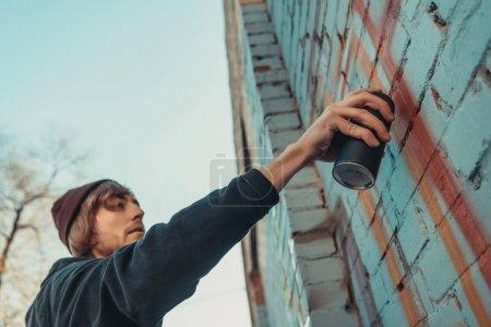 Photo pour Peinture colorée graffiti sur le mur du bâtiment d'homme - image libre de droit
