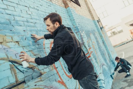 Photo for Street artists painting colorful graffiti on wall of building - Royalty Free Image