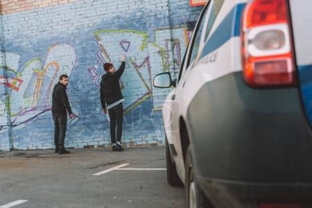 Foto de Vista posterior de vándalos pintar graffiti en la pared, coche de policía en primer plano - Imagen libre de derechos