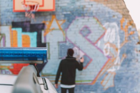 back view of vandal painting graffiti on wall, police car on foreground